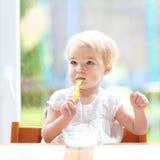 Gulligt behandla som ett barn flickan som äter yoghurt från skeden Arkivfoton