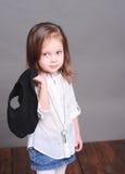 Gulligt behandla som ett barn flickan som poserar i studio Arkivbild