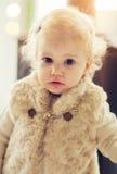 Gulligt behandla som ett barn flickan som poserar på utsmyckad kläder Royaltyfri Foto