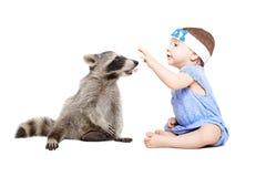 Gulligt behandla som ett barn flickan som spelar med tvättbjörnen Arkivfoto