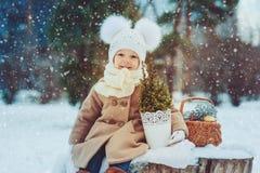 Gulligt behandla som ett barn flickan som tycker om vinter, går i snöig parkerar och att bära den varma hatten Arkivfoto