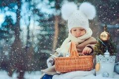 Gulligt behandla som ett barn flickan som tycker om vinter, går i snöig parkerar och att bära den varma hatten Arkivbild