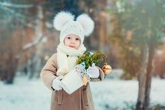 Gulligt behandla som ett barn flickan som tycker om vinter, går i snöig parkerar och att bära den varma hatten Arkivfoton