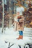 Gulligt behandla som ett barn flickan som tycker om vinter, går i snöig parkerar och att bära den varma hatten Fotografering för Bildbyråer