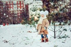 Gulligt behandla som ett barn flickan som tycker om vinter, går i snöig parkerar och att bära den varma hatten Arkivbilder