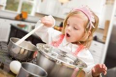 Gulligt behandla som ett barn flickan som spelar kocken With Pots och pannor i kök Royaltyfri Foto