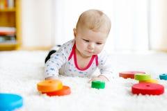 Gulligt behandla som ett barn flickan som spelar med den färgrika träpladderleksaken arkivbild