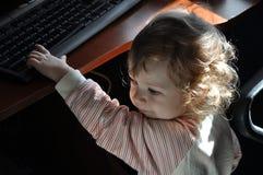 Gulligt behandla som ett barn flickan som spelar med tangentbordet fotografering för bildbyråer