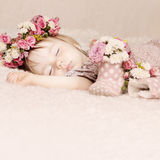 Gulligt behandla som ett barn flickasömn med blommatappning Royaltyfri Bild