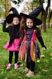Gulligt behandla som ett barn flickor i karnevaldräkter och stora svarta häxahattar under allhelgonaaftonberömmar i parkera arkivfoto