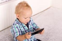 Gulligt behandla som ett barn hållande ögonen på tecknade filmer för pojken i smartphone Roligt litet barn som spelar med telefon Royaltyfria Foton