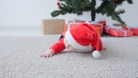 Gulligt behandla som ett barn i dräkten av Santa Claus som ser en gåva stock video