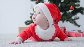 Gulligt behandla som ett barn i dräkten av Santa Claus som ser en gåva arkivfilmer