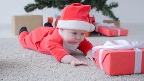 Gulligt behandla som ett barn i dräkten av Santa Claus som ser en gåva lager videofilmer