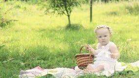 Gulligt behandla som ett barn i en krans på en picknick på en sommardag Arkivbild