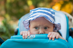 Gulligt behandla som ett barn i en Panama hatt som kikar ut ur sittvagnen Arkivfoto