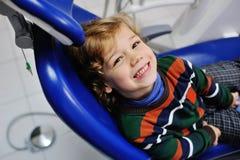 Gulligt behandla som ett barn i en randig tröja på mottagande på tandläkaren Royaltyfri Bild