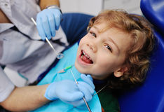 Gulligt behandla som ett barn i en randig tröja på mottagande på tandläkaren Arkivbild
