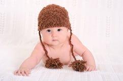 Gulligt behandla som ett barn i rolig brun hatt Arkivbild