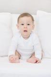 Gulligt behandla som ett barn i vit - sammanträde i vit säng Arkivbild