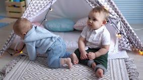 Gulligt behandla som ett barn klockor en annan unge som spelar med en girland nära barns tält arkivfilmer