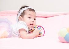 Gulligt behandla som ett barn leendet och spela leksaken på rosa färgfilten Royaltyfria Foton