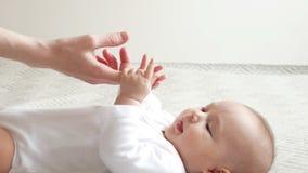 Gulligt behandla som ett barn lekar med moderns fingrar stock video