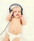 Gulligt behandla som ett barn lyssnar till musik i hörlurar som ligger på säng Arkivfoto
