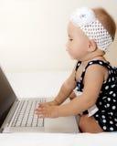 Gulligt behandla som ett barn med en bärbar dator Royaltyfri Foto