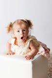 Gulligt behandla som ett barn med ett förvånat framsidauttryck Arkivfoto