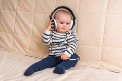 Gulligt behandla som ett barn med hörlurar lyssnar till musik hemma Royaltyfri Bild