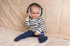 Gulligt behandla som ett barn med hörlurar lyssnar till musik hemma Fotografering för Bildbyråer