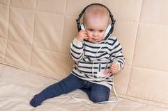 Gulligt behandla som ett barn med hörlurar lyssnar till musik hemma Royaltyfri Foto