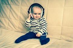 Gulligt behandla som ett barn med hörlurar lyssnar till musik hemma Royaltyfria Foton
