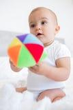 Gulligt behandla som ett barn med leksaksammanträde på säng Arkivbild