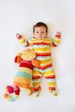 Gulligt behandla som ett barn med randig kulör pyjamas och en kattleksak som ligger på säng Fotografering för Bildbyråer