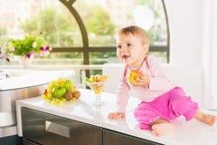 Gulligt behandla som ett barn på köket som rymmer en persika Arkivfoton