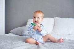 Gulligt behandla som ett barn pojken som hemma spelar med den stack leksaken på säng arkivfoto