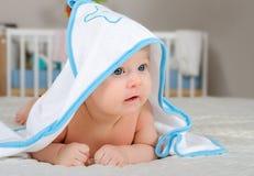 Gulligt behandla som ett barn pojken i en med huva handduk efter bad Arkivfoton
