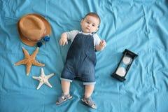 Gulligt behandla som ett barn pojken med att ligga för havsstjärnor arkivbild