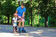 Gulligt behandla som ett barn pojken med den inline åka skridskor instruktören i parkeralearinien Royaltyfri Bild