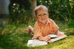 Gulligt behandla som ett barn pojken med exponeringsglas som ligger på grönt gräs som läser boken i sommardag Arkivbilder