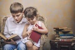 Gulligt behandla som ett barn pojken och flickan i en stol som läser en bok i en inre Royaltyfri Bild