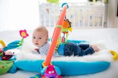 Gulligt behandla som ett barn pojken på den färgrika idrottshallen som hemma spelar med hängande leksaker Arkivbild