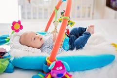 Gulligt behandla som ett barn pojken på den färgrika idrottshallen som hemma spelar med hängande leksaker Arkivbilder