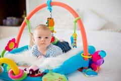 Gulligt behandla som ett barn pojken på den färgrika idrottshallen som hemma spelar med hängande leksaker Fotografering för Bildbyråer