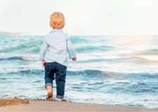 Gulligt behandla som ett barn pojken på stranden som beundrar havet oisolerad fot Lyckligt Royaltyfria Bilder