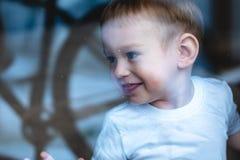 Gulligt behandla som ett barn pojken som ser i fönsterexponeringsglaset med reflexion r r royaltyfri bild