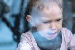 Gulligt behandla som ett barn pojken som ser i fönsterexponeringsglaset med reflexion r fotografering för bildbyråer