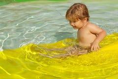 Gulligt behandla som ett barn pojken som glider från den gula watersliden Fotografering för Bildbyråer